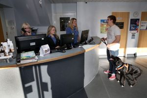 Client Stood at Reception Talking to Friendly Receptionists