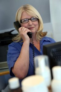Receptionist Assisting a Client Over the Phone
